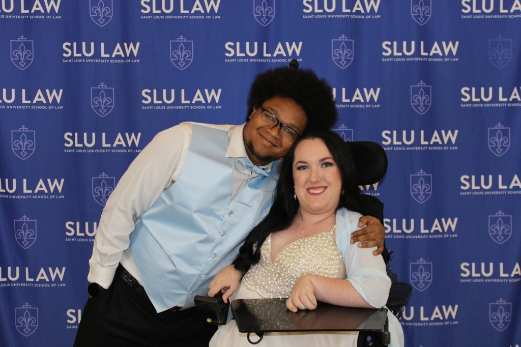 A Black man with his arm around white woman in front of a blue backdrop that says SLU LAW in white lettering. The man is wearing a white dress shirt, black dress pants, and a light blue vest and bow tie, and he wears glasses and has a goatee and afro. The woman sits in a wheelchair with a tray in front and is wearing a pale pink dress with a pearl bodice and a light blue shawl. She has long black hair.