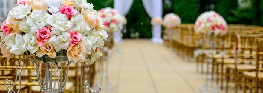 An empty wedding aisle with flowers in focus at the forefront and a marriage altar out of focus in the background.