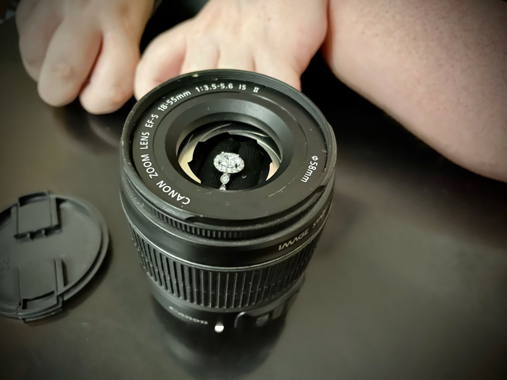 An oval-shaped diamond engagement ring with a halo of stones and a silver band inside of a customized ring box made from a Canon camera lens. White female arms are out of focus in the background and the lens cover is next to the lens box.